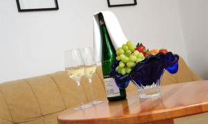 Doppelzimmer, Weinfalsche mit Gläsern und Weintrauben am Tisch.
