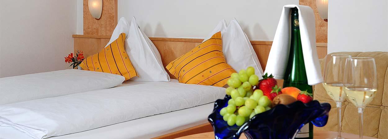 Doppelzimmer mit Tisch, Obstkorb und Sekt