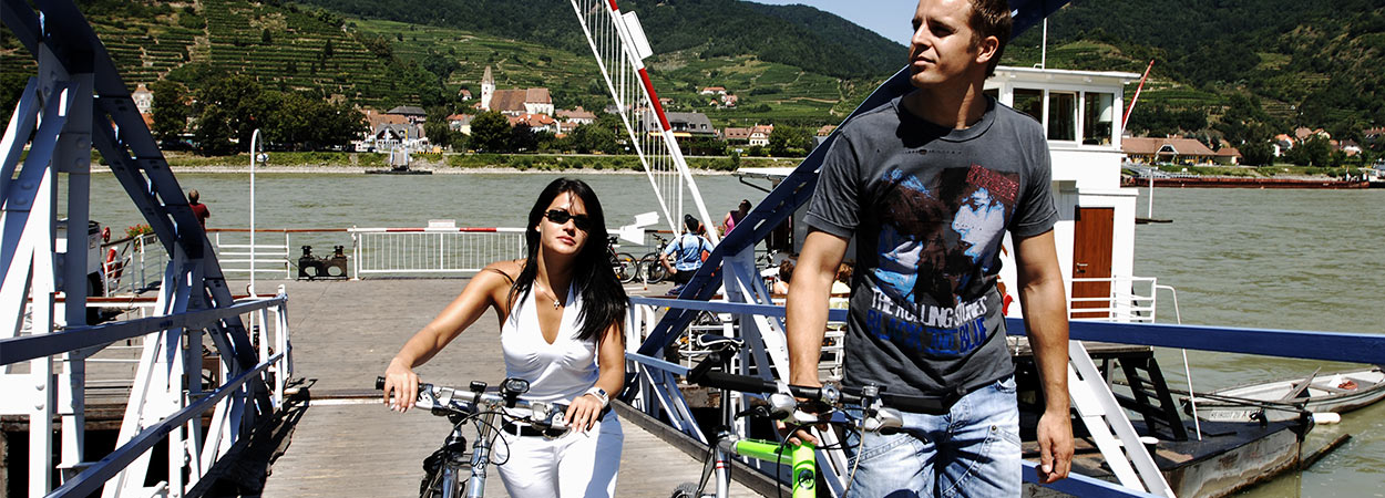 Pärchen schiebt Fahrräder von der Fähre in Spitz an der Donau