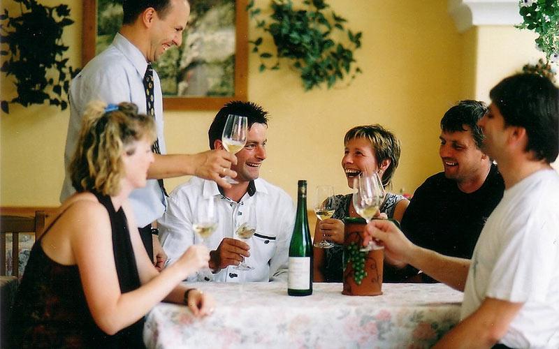 Restaurant: Personen stoßen mit Weißwein an.